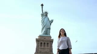 Happy excited successful Caucasian female student jumping with joy at Statue of Liberty monument in USA slow motion.