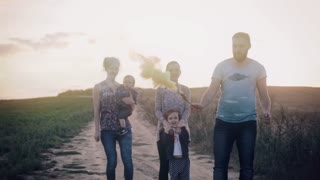 Happy family of five people spending time outdoors. Father holding a smoke grenade in nature and running with fume