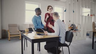 Happy female manager helps multiethnic colleagues, walks away. Teamwork and cooperation in modern trendy loft office 4K.