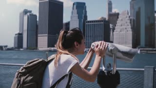 Happy female traveler looks through a tower viewer at epic sunny cityscape skyline of Manhattan, New York slow motion.