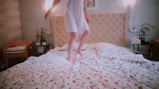 Happy fresh brunette woman in night dress jumping on bed, having fun. Beautiful girl feeling happy in the morning.