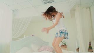 Happy fresh woman wearing pajamas jumping on her bed in morning. Beautiful girl having fun. Slow motion.