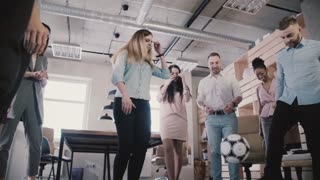 Happy friends play with ball in modern healthy office. Casual employees enjoy physical activity during break slow motion
