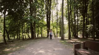 Happy groom is running with his laughing bride on his back. Happy couple having fun on their wedding day. Steadicam shot