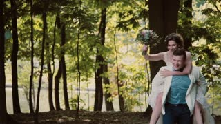 Happy groom is running with his laughing bride on his back. Happy couple having fun on their wedding day.