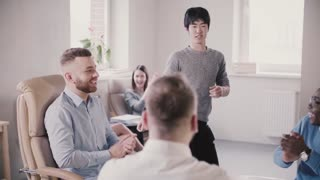 Happy Japanese office worker doing very funny victory dance walk in modern loft office celebrating success slow motion.