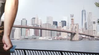 Happy male traveler runs up to epic famous Brooklyn Bridge river bank fence skyline of New York City, jumps cheerfully.