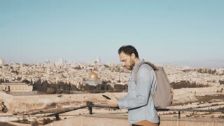 Happy man takes selfie in old town Jerusalem. Bearded local male smiles happy, taking photos. Perfect Israel panorama 4K
