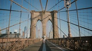 Happy man talking on phone, walking away from camera back view along Brooklyn Bridge, New York on a hot summer day 4K.