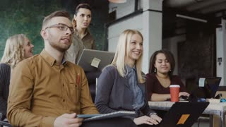 Happy mixed race group of people at loft office. Man and woman with laptop, tablet at business lecture listening speaker
