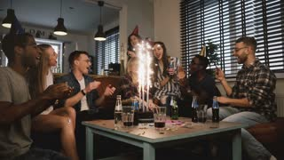 Happy multi ethnic friends birthday party with cake and sparkling firework. Diverse friends sing Happy Birthday, hug. 4K