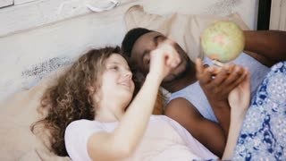 Happy multiethnic couple and twisting the globe to choose the location to traveling. Man and woman lying on the bed.