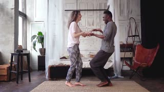 Happy multiethnic couple in pajamas dancing together. Maw and woman hugs, falls on the bed and kisses. Slow motion.