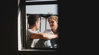Happy multiethnic man and woman sitting together at beautiful sunny balcony, looking at each other, talking about life.
