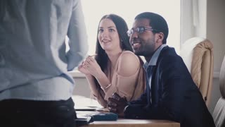 Happy multiethnic team listening to unrecognizable male executive, smiling at office meeting slow motion close-up.