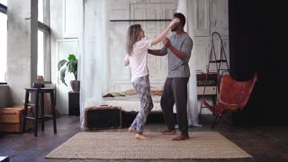 Happy multiracial couple in pajamas holding hands and dancing. Woman and man in cheerful mood have fun. Slow motion.