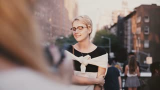 Happy peaceful European blonde girl with short hair in eyeglasses smiling at photoshoot outside, posing at camera.