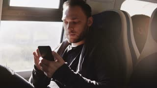 Happy relaxed European freelance worker using smartphone messenger app enjoying comfortable traveling on the train.