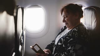 Happy senior female airplane passenger using smartphone messenger app, enjoying the view and smiling on the window seat.