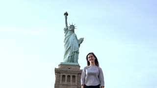 Happy smiling European woman stands looking at camera and posing at Statue of Liberty in sunny New York slow motion.