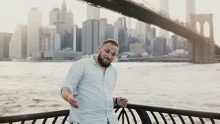 Happy successful Caucasian man smiling at camera, showing gestures, pointing at amazing New York urban scenery behind 4K