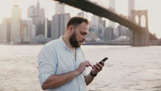 Happy successful European businessman makes a phone call on smartphone, talking and smiling near Brooklyn Bridge 4K.