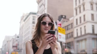 Happy thoughtful European female beauty blogger in sunglasses using smartphone shopping app in New York slow motion.