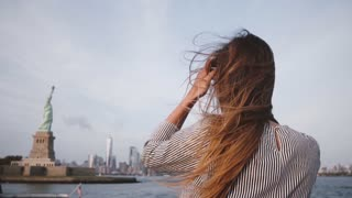 Happy traveler woman with hair blowing in the wind enjoying New York skyline at Statue of Liberty on a boat slow motion.