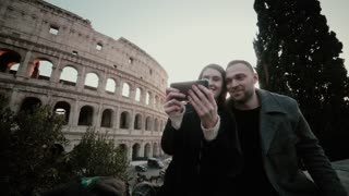 Happy traveling couple taking selfie photo on smartphone near the Colosseum in Rome, Italy together, for memories.