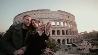 Happy young couple taking a selfie photo near the Colosseum in Rome, Italy. Handsome man kisses woman, smiling.