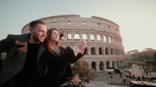 Happy young couple taking a selfie photo near the Colosseum in Rome, Italy. Traveling man and woman smiling in camera.