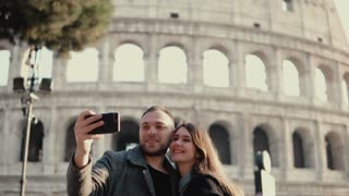 Happy young couple using smartphone for taking selfie photo near Colosseum in Rome, Italy. Man and woman have vacation.