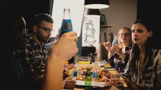 Happy young multiethnic friends celebrating, eating pizza and having drinks at casual party by kitchen table slow motion