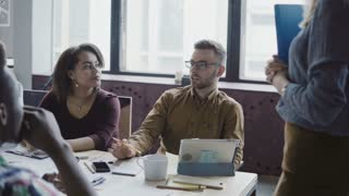 Happy young team working at loft office, discussing project. Female leader giving direction mixed race group of people.