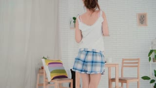 Happy young woman dancing in kitchen wearing pajamas in the morning. Brunette girl having fun during breakfast.