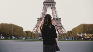 Happy young woman feeling joy because of seeing Eiffel tower in Paris, France. Girl smile at camera and send blow kiss.