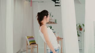 Happy young woman standing in light apartment wearing pajamas. Smiling girl have fun in the morning. Slow motion.