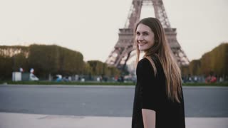 Happy young woman walking near the Eiffel tower in Paris, France, girl looking at camera and smiling to somebody.