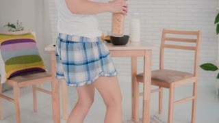 Happy young woman wearing pajamas preparing flakes for breakfast and dancing in light kitchen. Having fun in morning.