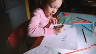 High angle camera sliding right over little Caucasian girl child in pink sweater drawing with colorful pencils at table.