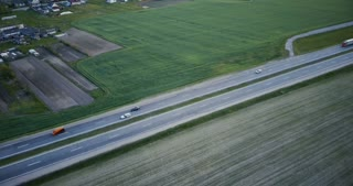 Highway aerial panorama with field and village. Drone 4K panning tilt shot. Logistics transportation network industry.
