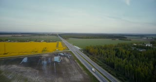 Highway road in valley with forest canola field. Aerial drone 4K shot traffic cars and trucks. Agricultural industry.