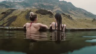 Hot spring geothermal spa in Iceland. Two traveling woman relaxing in hot pool with beautiful landscape on mountain.