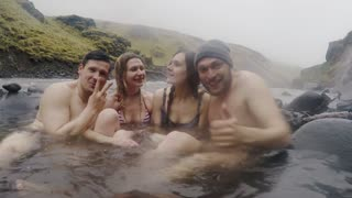 Hot spring geothermal spa on Iceland. Two traveling couple relaxing in hot pool on Iceland. Tourists enjoying bathing.