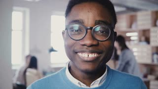 Incredible close-up portrait of handsome young African American man in glasses smiling at camera in busy office 4K.