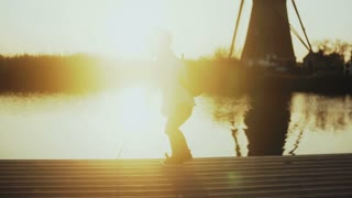 Kid playing with a stick on sunset lake pier. Back view. Little explorer. Amazing sunlight lens flare horizon. 4K.