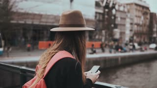 Lady with red backpack stands on river bridge. Girl in stylish hat with long hair and a phone waiting. 4K back view.