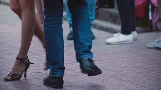 Legs of two professional dancers doing a Latino dance and having fun at a dance party event in the street slow motion.