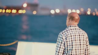 LITHUANIA, KLAIPEDA 30 August 2014. A middle-aged man in a plaid shirt is looking at the port from the pier in evening.