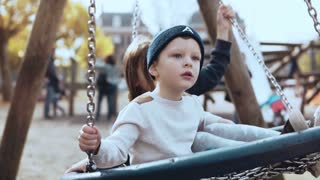 Little boy and girl on a nest swing in sunny park. Thoughful children friends swing together. Slow motion side view.